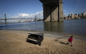 A child runs past a grand piano that has been left by the East River underneath the Brooklyn Bridge in New York